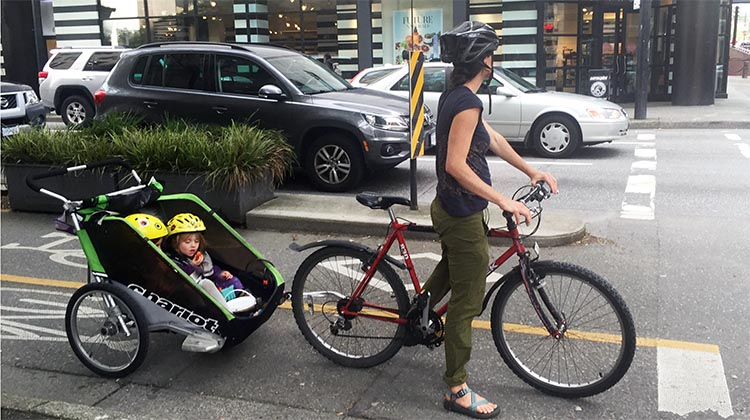 f86bb4e6b7c Mom and two kids cycle in relative safety on the Dunsmuir Street separated  bike lane in downtown Vancouver